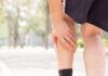 Zapalenie ścięgna Achillesa - mężczyzna trzymający się za łydkę