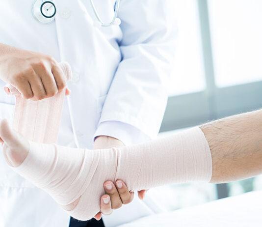 Złamanie zmęczeniowe - lekarz bandażujący nogę pacjenta